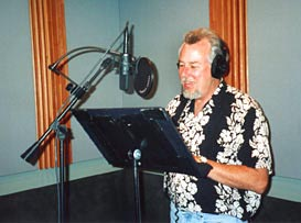 Picture of Michael Knott in the studio recording voice over narration. Mike is a narrator, announcer, voice actor with a deep baritone speaking and deep bass singing voice like Bary White, and a funny cartoon voice with his own recording studio.